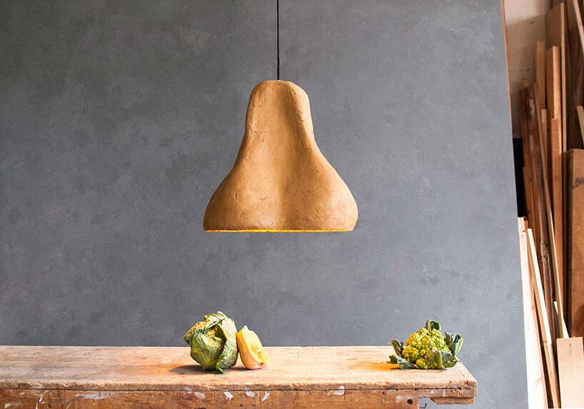 wyjątkowa żółta lampa wisząca Sensi projektu Maria Fiter od Crea-Re Studio wisząca nad starym drewnianym stołem