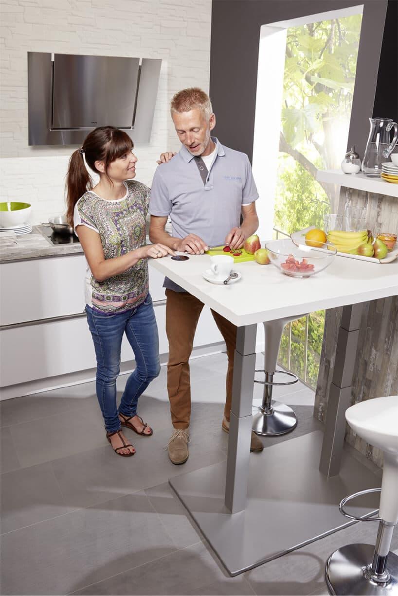 dwie osoby stojące przy blacie zchromowaną nogą wmałej kuchni zwysokim oknem