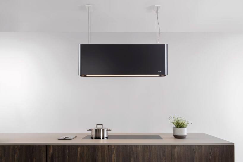 czarna lampa kuchenna nad piecem indukcyjnym ze srebrnym garnkiem wjasno brązowym stole