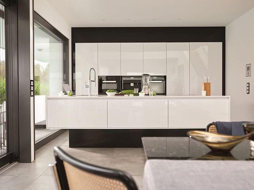 biały aneks kuchenny czarny stół brązowe krzesła