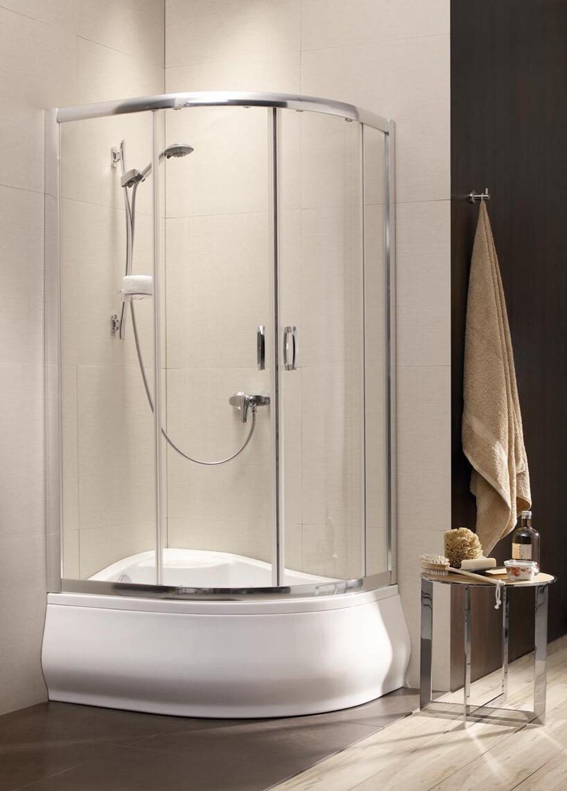 szklany prysznic zbiała ceramiczną wanną stoliczek zkosmetykami brązowy ręcznik na ścianie zpłytek