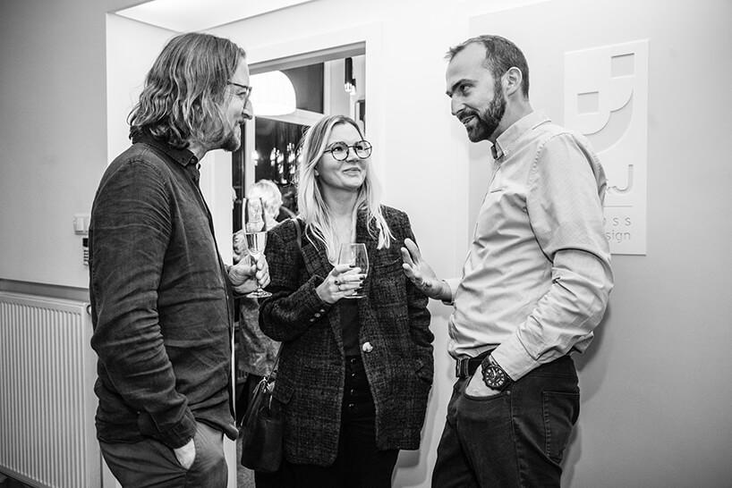 trzy osoby podczas rozmów na otwarciu Chłodna 11 concept showroomu J&J glass & design