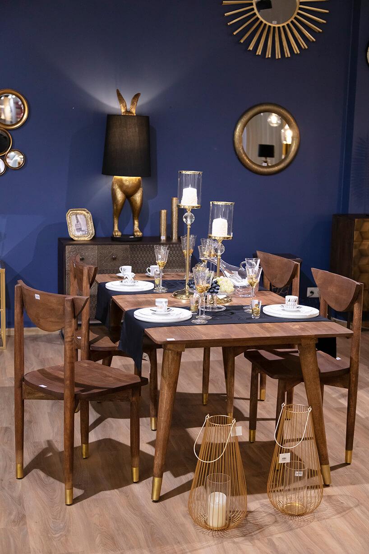 drewniany stół zdrewnianymi krzesłami podbitymi złotą blaszką zbiałą zastawą na tle