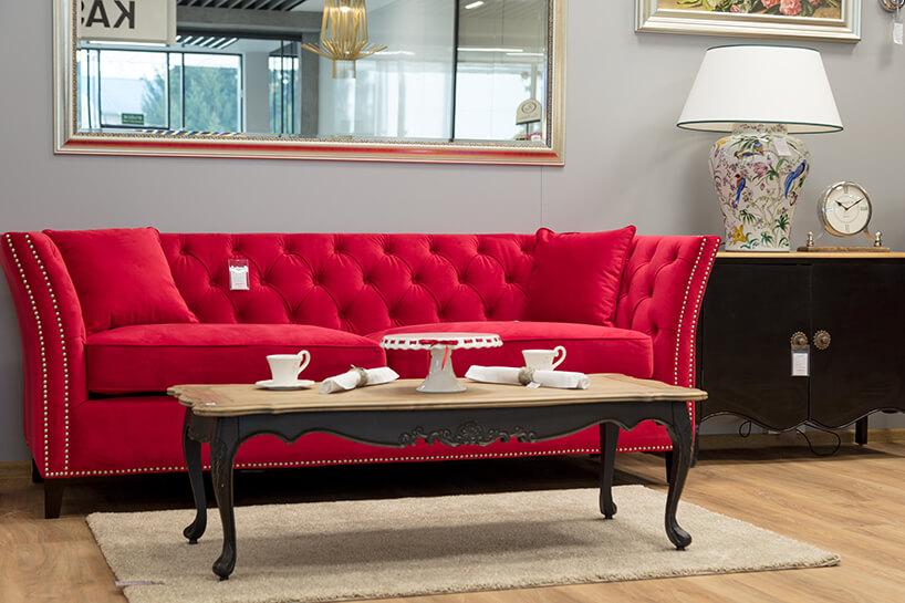 czerwona sofa na krótkich czarnych drewnianych nogach jako tło dla niskiego eleganckiego zdobionego stolika