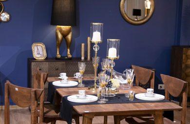 drewniany stół z drewnianymi krzesłami podbitymi złotą blaszką z białą zastawą na tle