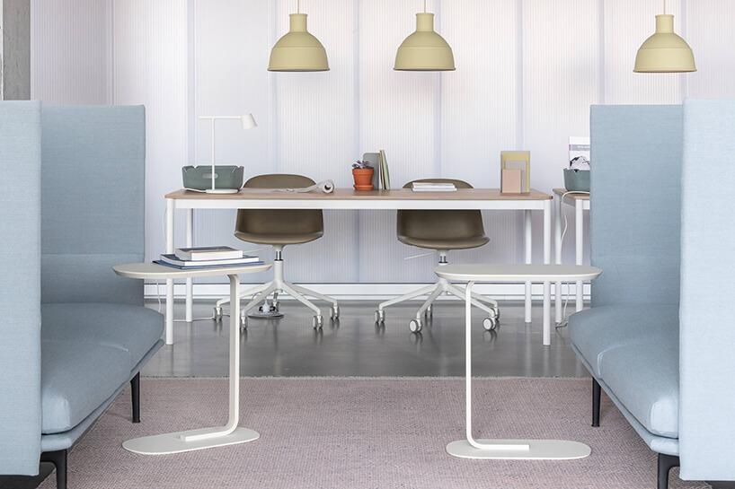 aranżacja miejsca pracy zprostym biurkiem idwoma niskim fotelami na kółkach