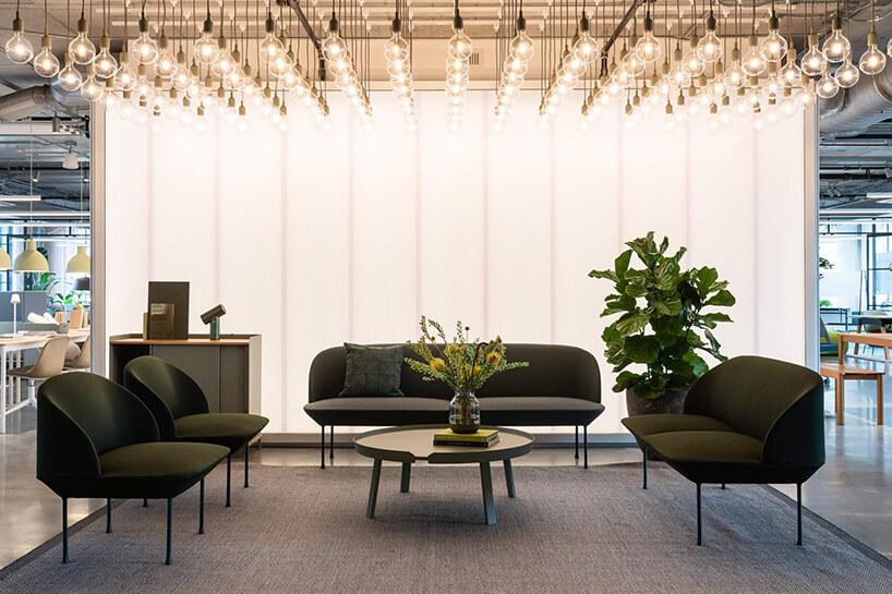 duża imała brązowa sofa przy okrągłym stoliku mocno oświetlona wieloma żarówkami