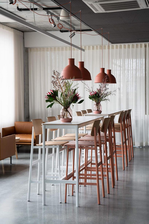 wysoki stolik zbiałymi ipomarańczowymi wysokimi stołkami