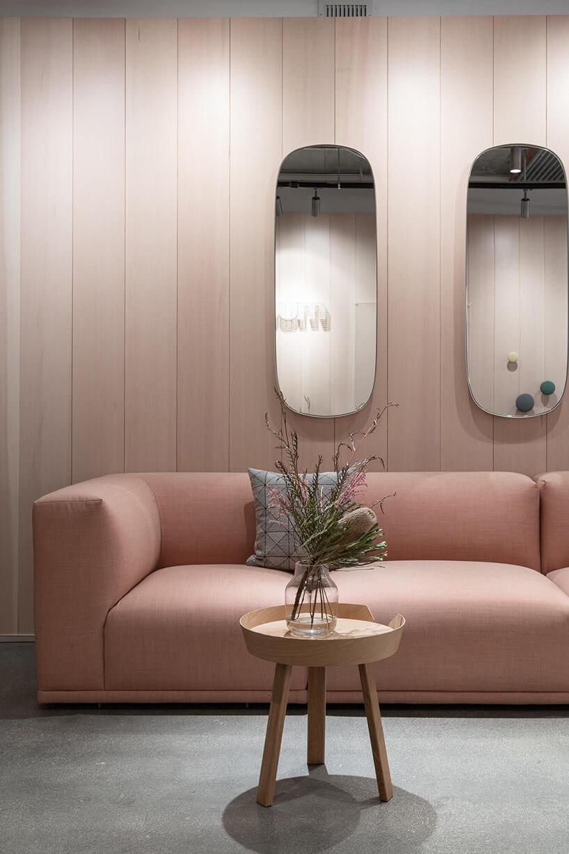 jasno różowa sofa pod dwoma lustrami zaokrąglonymi lustrami