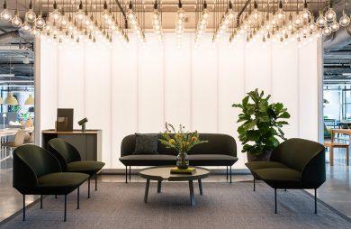 duża i mała brązowa sofa przy okrągłym stoliku mocno oświetlona wieloma żarówkami