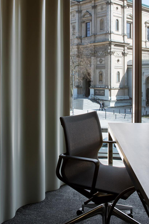 krzesło biurowe przy stole na tle okna