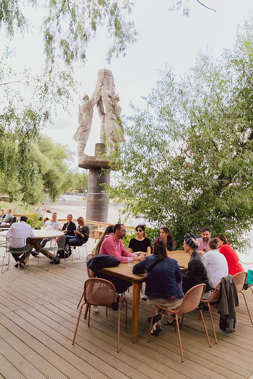 goście otwarcia Letniej Strefy Domoteki 2019 przy stolikach na tle rzeźby iWisły