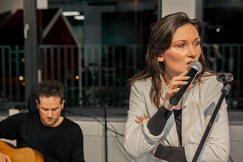 kobieta śpiewająca obok gitarzysty