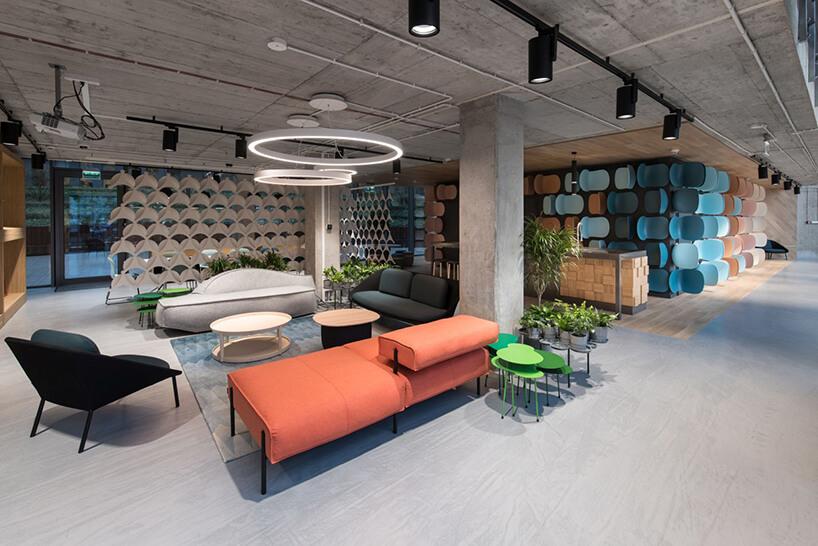 nowoczesna pomarańczowa sofa przy zielonym stoliku na tle czarnej sofy pod nowoczesną lampą wiszącą zwkształcicie koło