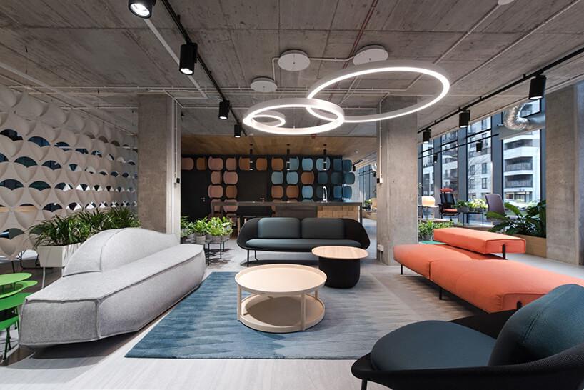 beżowy stolik na niebieskim dywanie pomiędzy czarnym fotelem szarą sofą czarną sofa ipomarańczową sofą