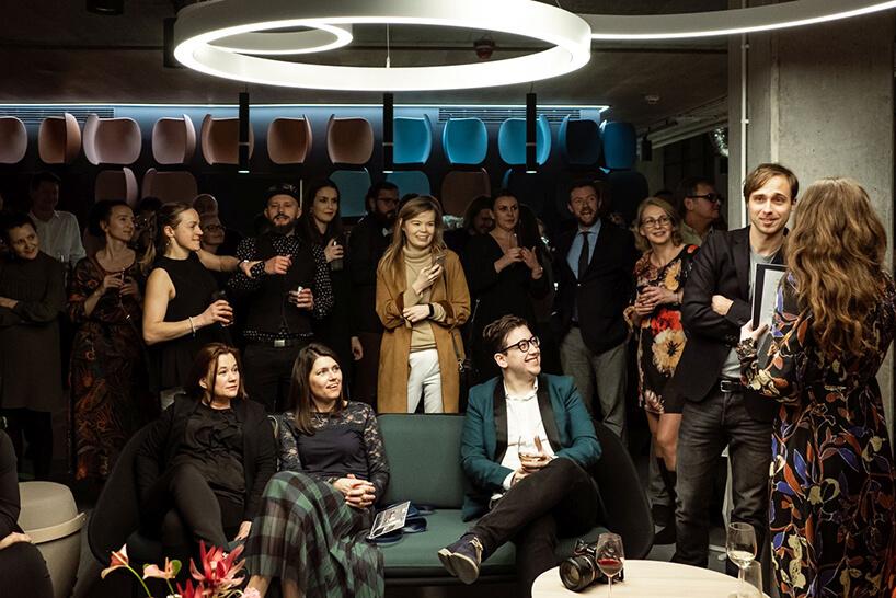 goście podczas otwarcia showroomu na tle ściany zplastikowymi siedziskami