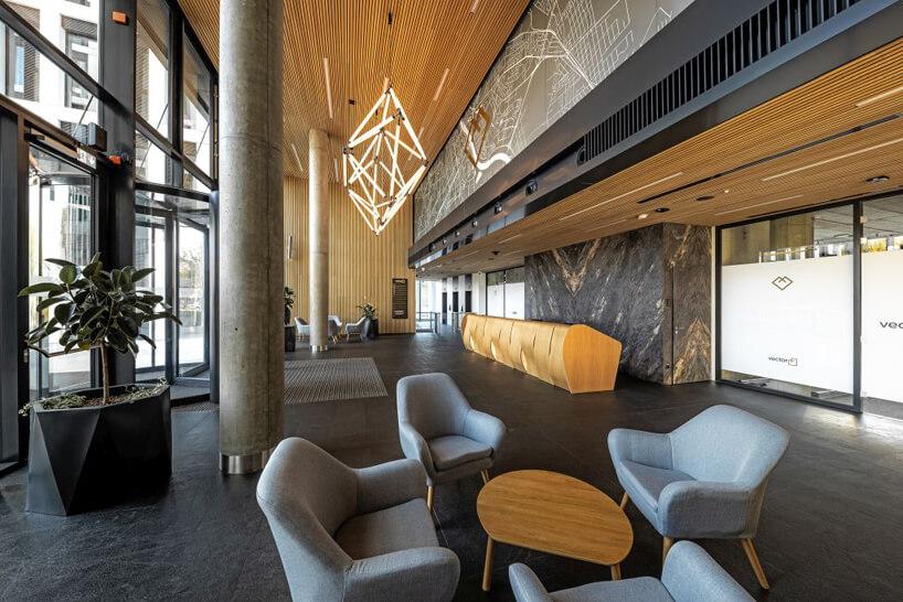 nowoczesny biurowiec Vector+ elegancka ciemna poczekalnia zniebieskim fotelami idrewnianym stolikiem na ciemnej kamiennej podłodze