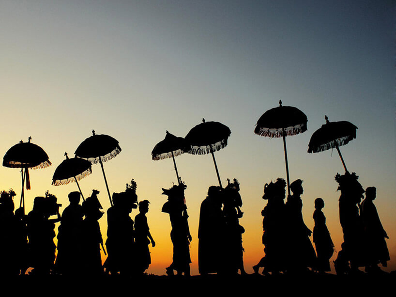 tłum ludzi zparasolami podążających drogą