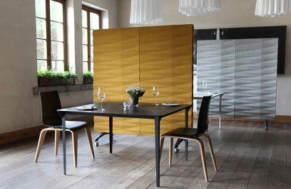 dwa czarne krzesła i stół przy słomkowej ścianie