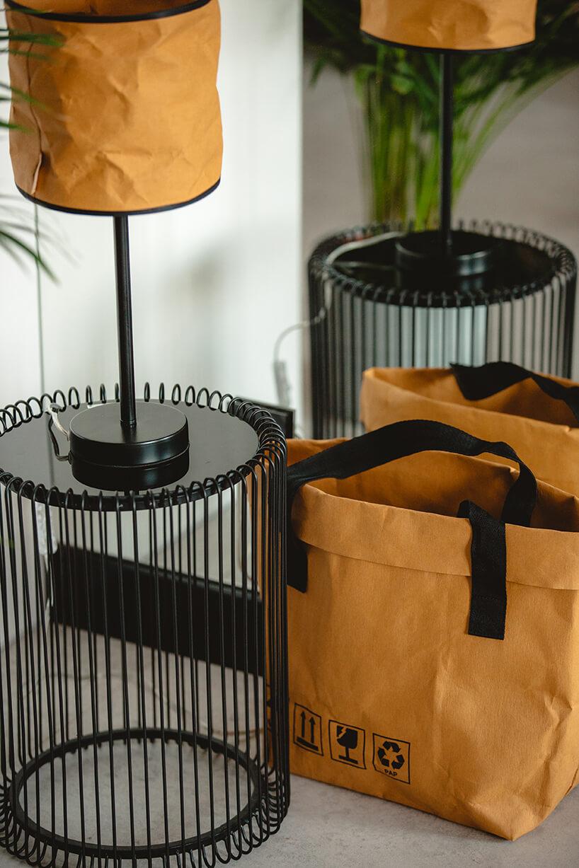 różne odporne torby zpapieru od Papedy obok wyjątkowych lamp zkloszami zpapieru na czarnych stolikach