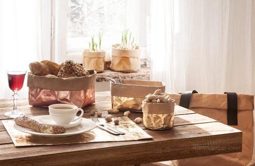 różne odporne pojemniki z papieru od Papedy na zastawionym stole z drewnianym blatem