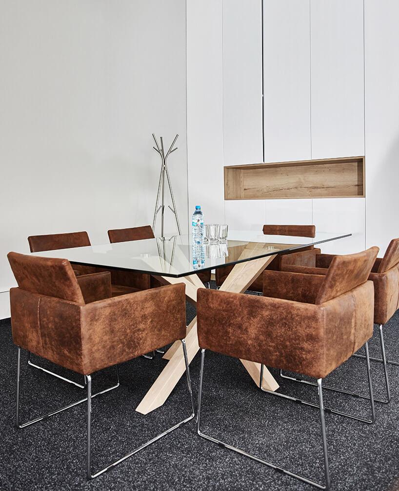 brązowe fotele przy szklanym stole