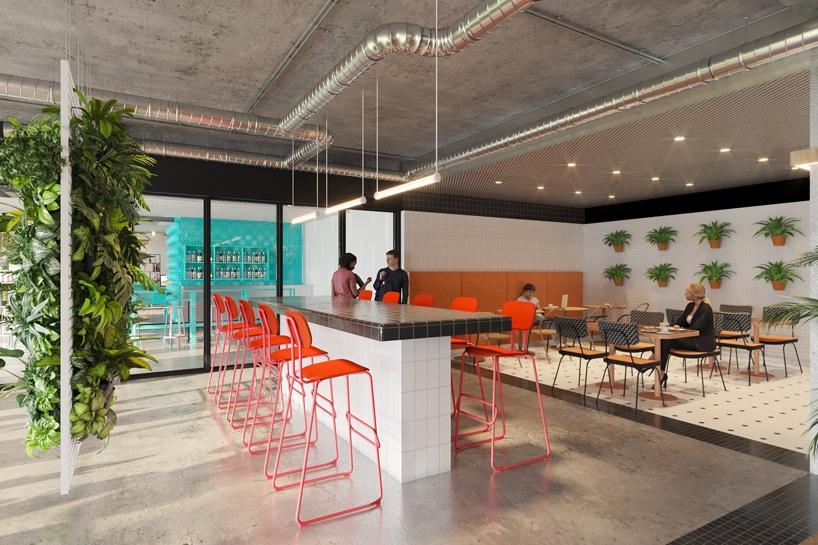 wnętrze Cukrownia Żnin Parku Industrialnego projektu MIXD przestrzeń jadalna zbiało czarną wusoką wyspą zpomarańczowymi krzesłami