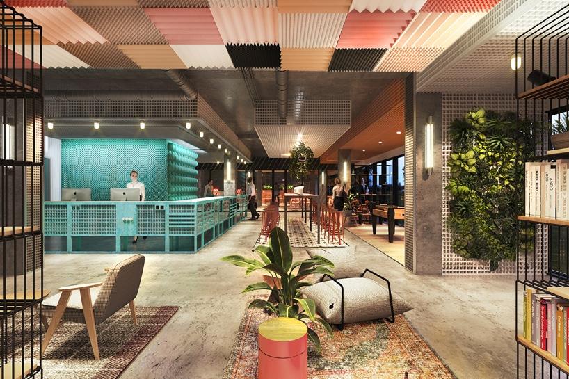 wnętrze Cukrownia Żnin Parku Industrialnego projektu MIXD recepjca zbetonową podłogą pod kolorowymi przestrzennymi panelami pod sufitem