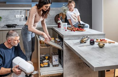 rodzina w kuchni podczas wyjmowania rzeczy szafki