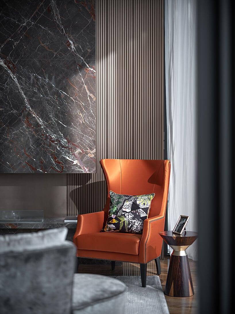 pomarańczowy zamszowy fotel retro na tle długiej zasłony wkolorze szarości
