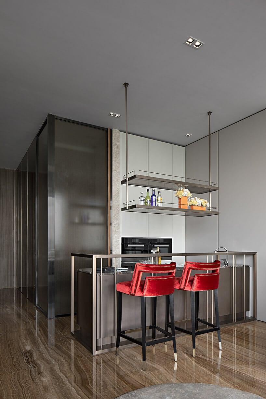 kuchnia zmetalową konstrukcją jako blat oraz Czerwonymi hokerami