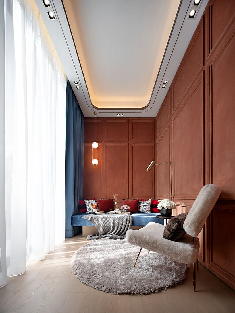 mały podłużny pokój pokryty miękkim materiałem na ścianach wkolorze ciemnego pomarańczu zbiałym długowłosym dywanikiem