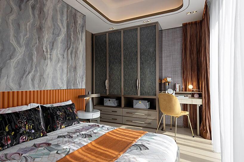 łóżko zwymyślną grafiką oraz pomarańczowym akcentem wsypialni zszarymi dodatkami