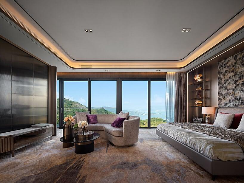 duża sypialnia zmiejscem do siedzenia przy dużych witrynach wsypialni zpodświetlanym sufitem