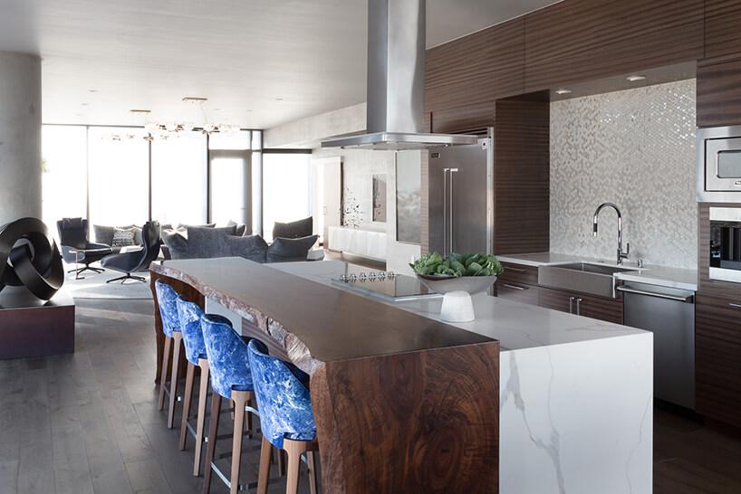 wnętrze penthouse'u od Benning Design Construction brązowa kuchnia zbiałą wyspą zkamienia iwysokim ciemnym drewnianym stołem zczterema krzesłami zniebieskim oparciem