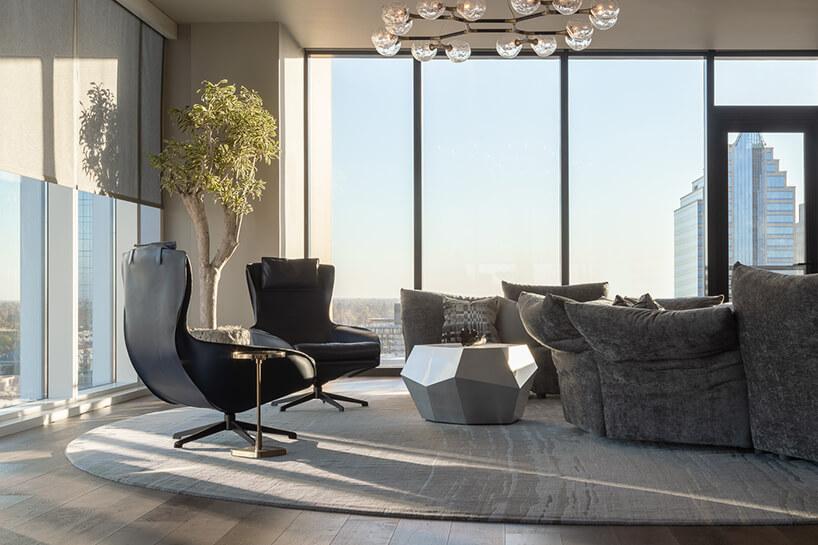 wnętrze penthouse'u od Benning Design Construction przestronny salon na tle przeszklonych ścian zdwoma wyjątkowym czarnymi fotelami obok srebrnego stolika