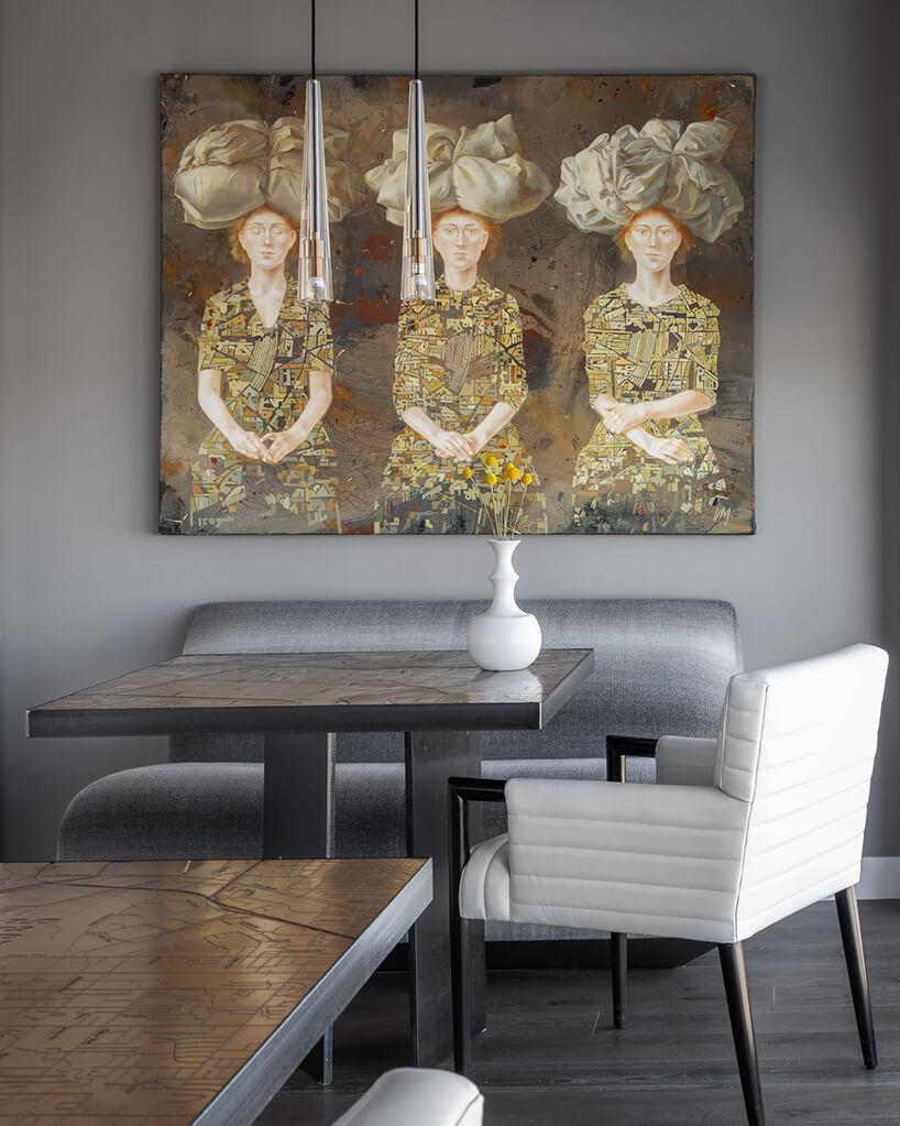 wnętrze penthouse'u od Benning Design Construction dwa stoliki ze złobionymi elementami na blatach na tle srebrnego siedziska pod obrazem ztrzema siedzącymi kobietami