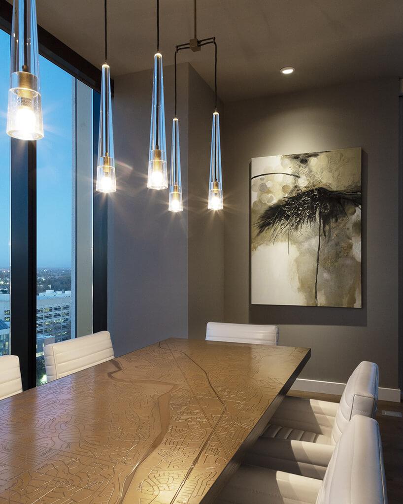 wnętrze penthouse'u od Benning Design Construction duży elegancki stół zwygrawerowanym planem miasta zbiałym krzesłami zpoziomymi przeszyciami
