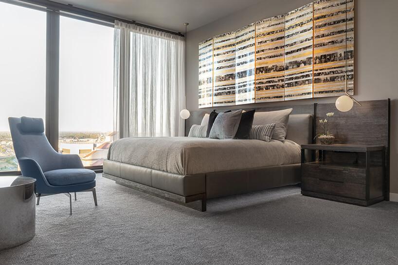 wnętrze penthouse'u od Benning Design Construction sypialnia panoramicznym oknem zniebieskim fotelem zzagłówkiem idużym ciemny łóżkiem