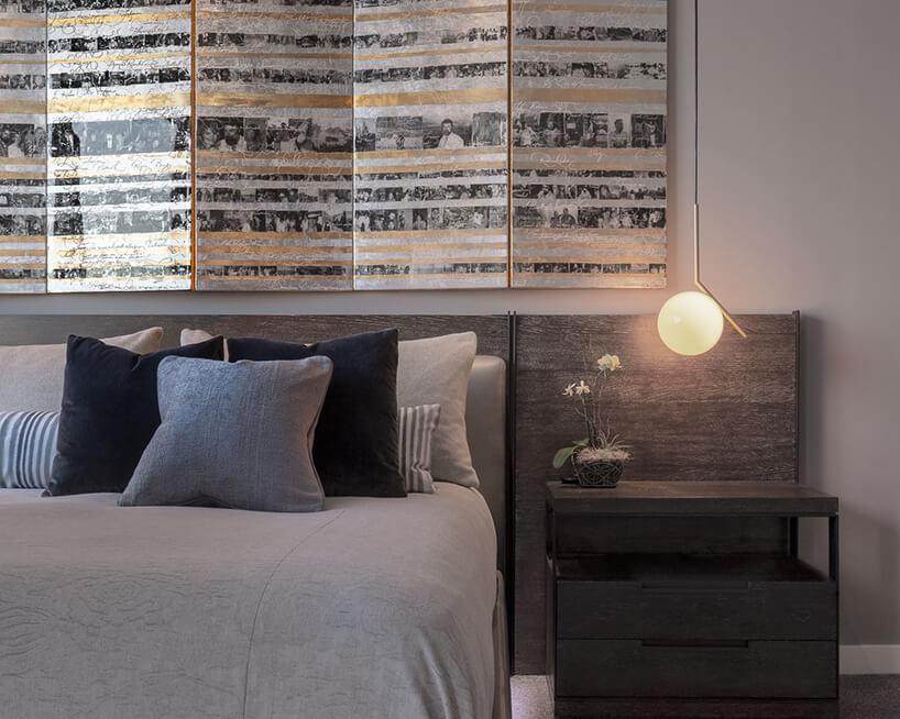 wnętrze penthouse'u od Benning Design Construction duże łóżko wsypialni na tle ściany zdrewnianym obiciem iwyjątkową wisząca lampą zmałym szklanym kloszem
