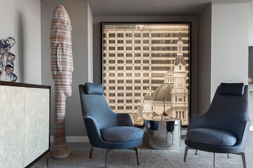 wnętrze penthouse'u od Benning Design Construction dwa eleganckie niebieskie fotele obok białej wysokiej rzeźby zkolorowymi paskami ibłyszczącym srebrny stolikiem