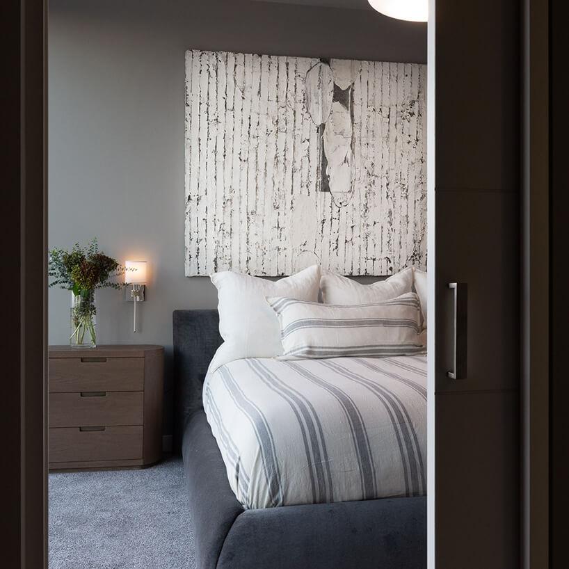 wnętrze penthouse'u od Benning Design Construction elegancka mała sypialnia zbrązową szafką przy łóżku ibiałym obrazem nad łózkiem