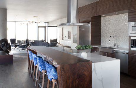 wnętrze penthouse'u od Benning Design Construction brązowa kuchnia z białą wyspą z kamienia i wysokim ciemnym drewnianym stołem z czterema krzesłami z niebieskim oparciem