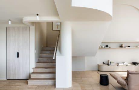 dwupoziomowy penthouse M w australijskim Gold Coast projektu CJH Studio jasne ściany salonu i drewniane łamane schody obok beżowej sofy
