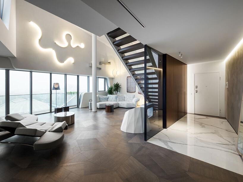 elegancki penthouse od Zaha Hadid elegancki wysoki salon zciemną drewniana podłoga iciemnymi schodami na górę