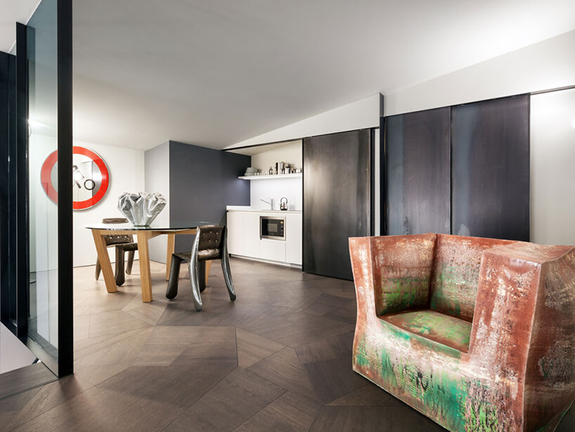 elegancki penthouse od Zaha Hadid nowoczesne wnętrze jadalni zkuchnią ze stołem ze szklanym blatem iwyjątkowymi krzesłami
