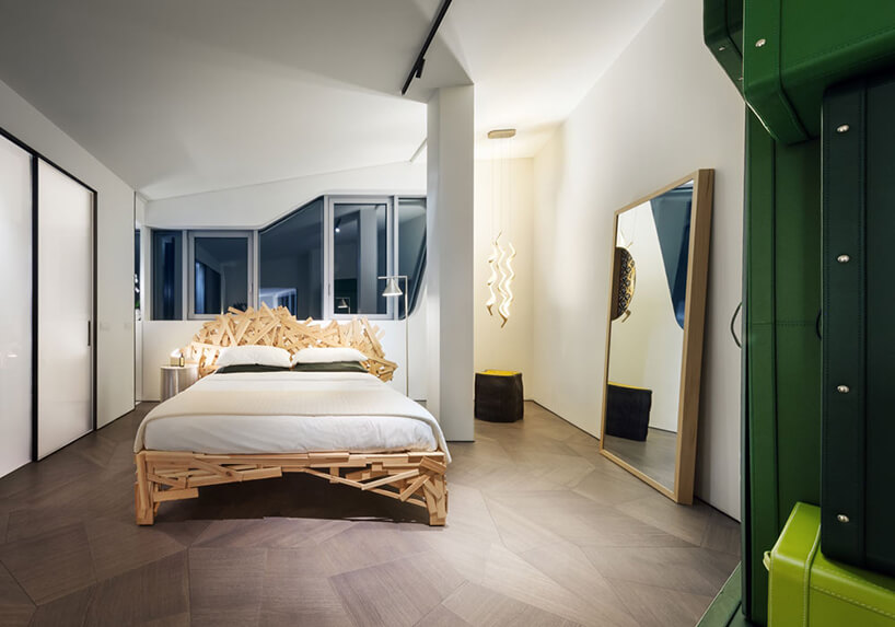 elegancki penthouse od Zaha Hadid biała sypialnia zduzym łóżkiem wykończonym małymi deseczkami oróżnych wielkościach