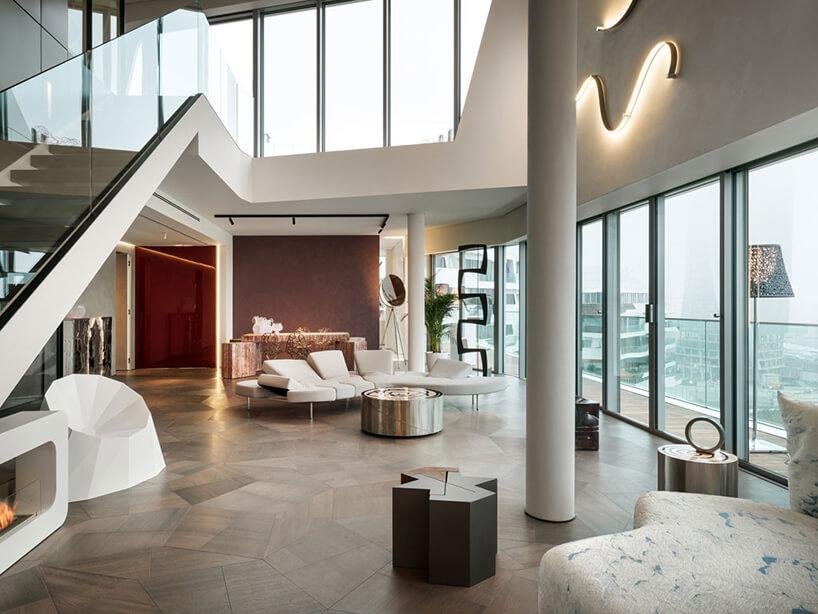 elegancki penthouse od Zaha Hadid widok na salon iantresolę ze schodami ze szklaną balustradą