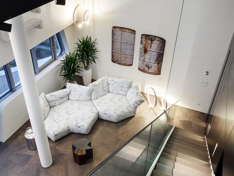 elegancki penthouse od Zaha Hadid widok zantresoli na wyjątkową biało niebieska sofą wgeometrycznych figurach