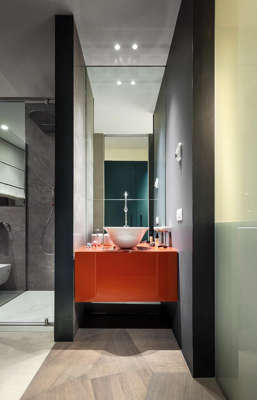 elegancki penthouse od Zaha Hadid łazienka zszarymi ścianami wolnostojąca umywalką na pomarańczowej szafce